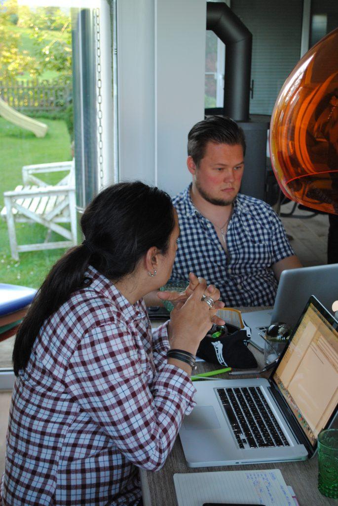 Tanja Albrecht und Patrick Dahm von Taeglich.ME sitzen gemeinsam am Tisch und arbeiten an ihren Laptops