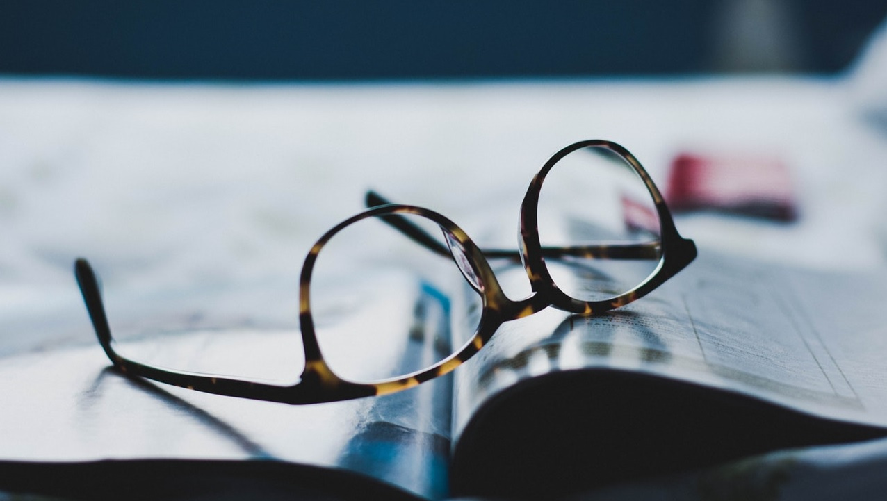 Brille liegt auf einem Magazin.