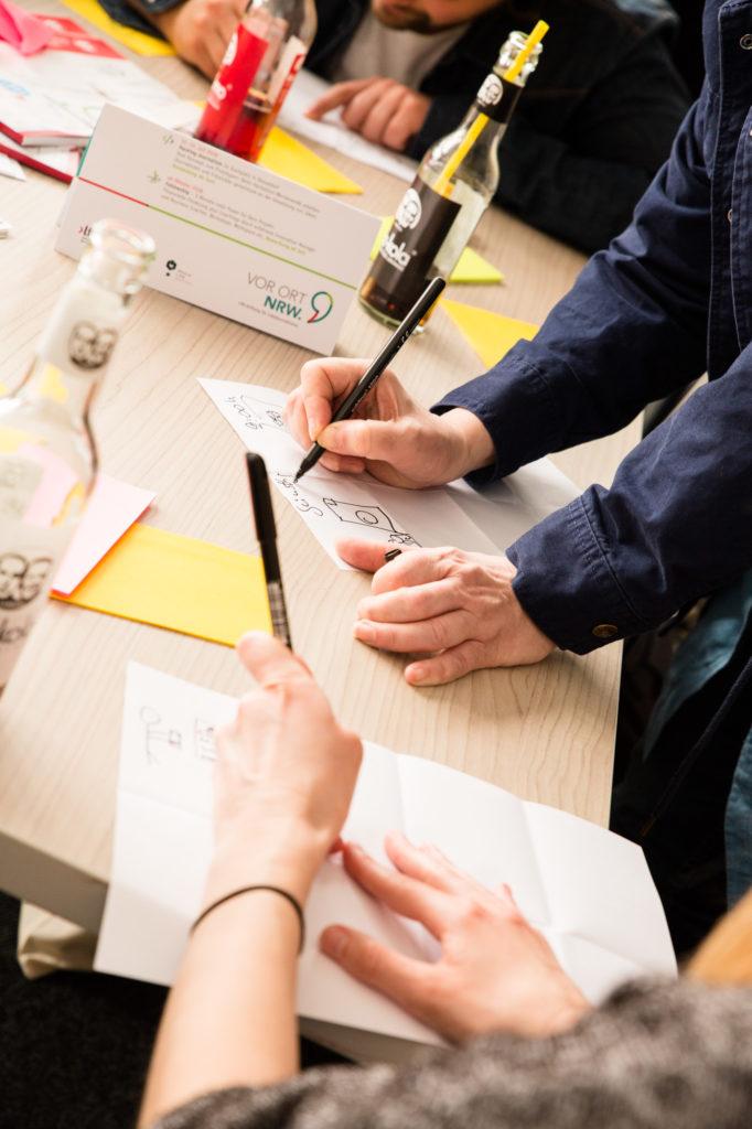 Teilnehmer des Idea Sprint 2018 schreibt etwas auf.