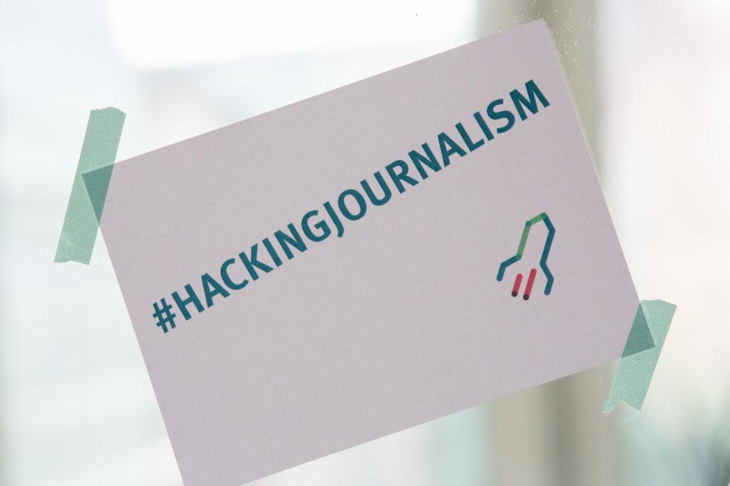 Der Hashtag #HACKINGJOURNALISM auf einer Postkarte.
