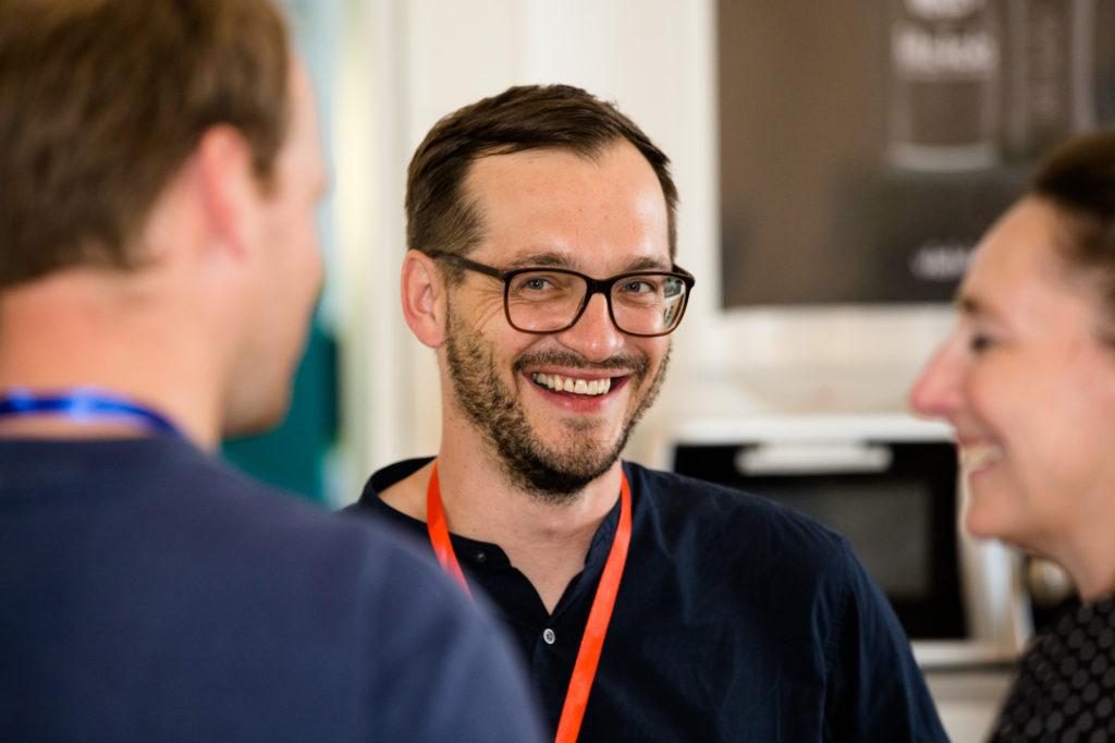 Ein Teilnehmer des Hackathons lächelt in die Kamera.