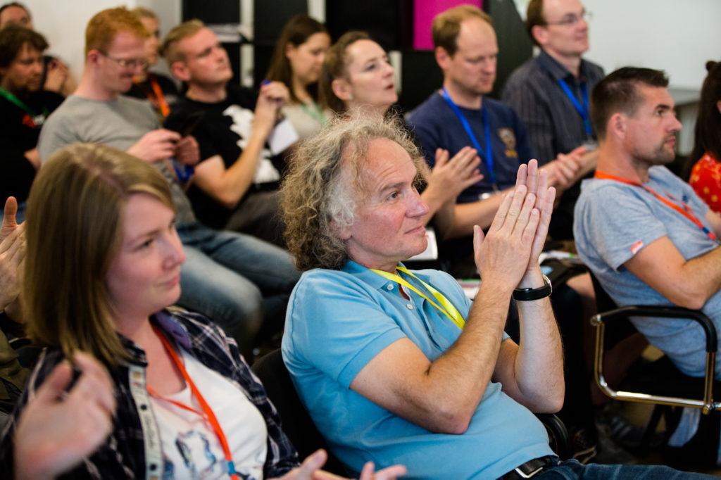 Teilnehmende des Hackathons 2018 lauschen gespannt und applaudieren.