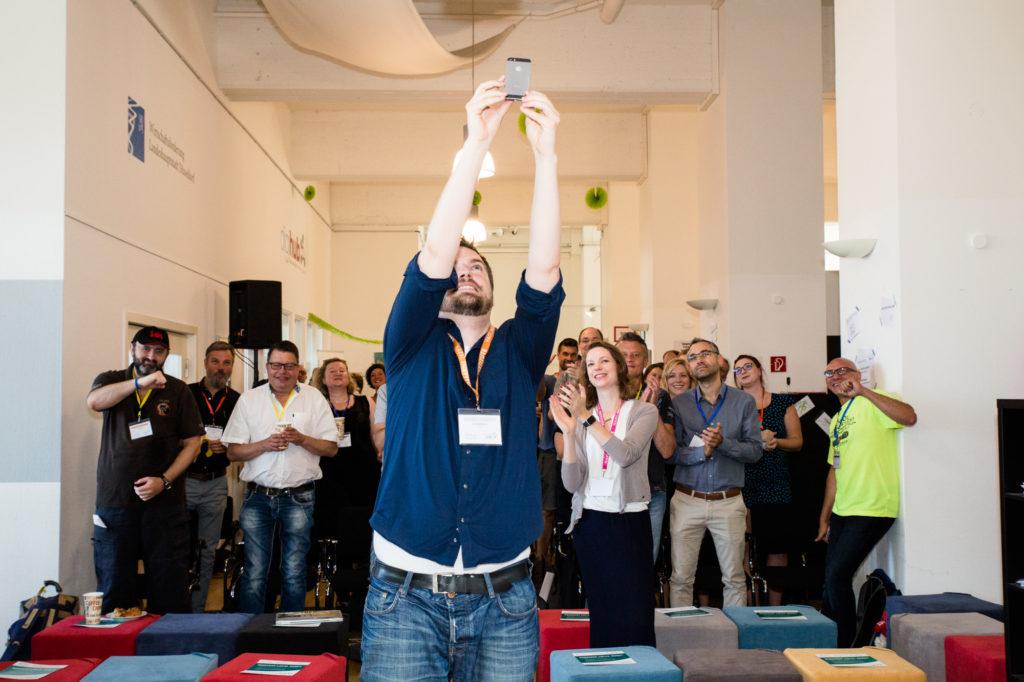 Johannes Meyer macht ein Gruppen-Selfie mit allen Teilnehmenden des Hackathons.