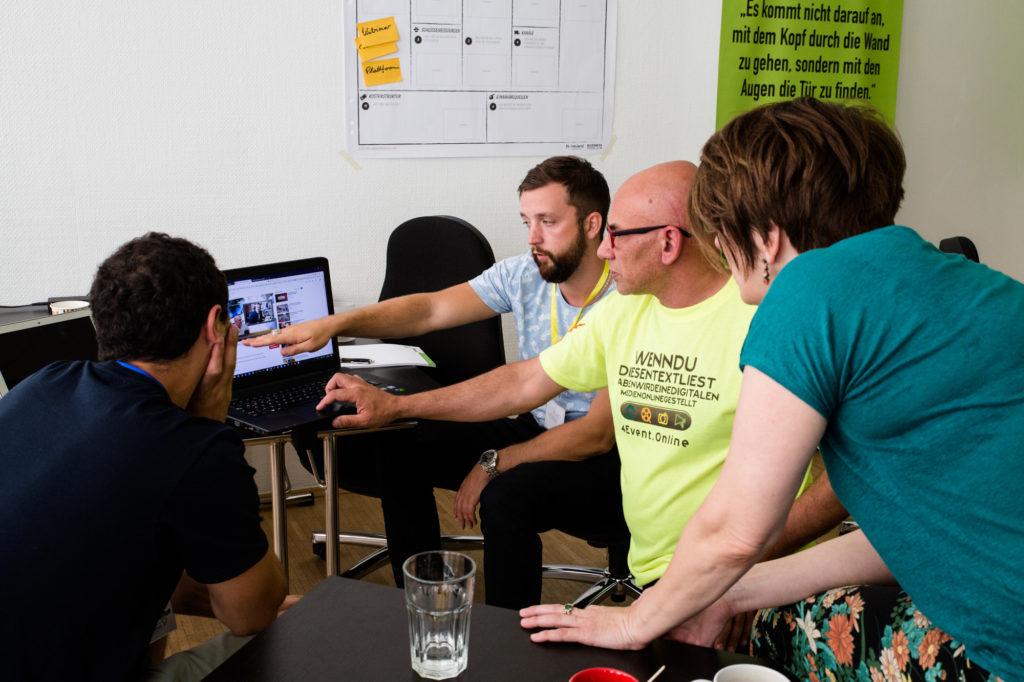 Teilnehmende des Hackathon probieren etwas am Computer aus.