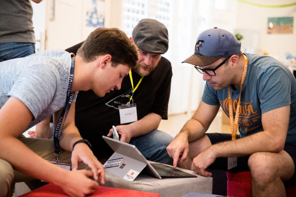 Teilnehmende des Hackathon 2018 arbeiten an einem PC.