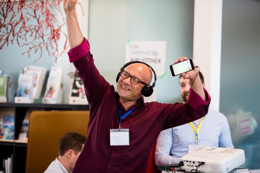 Ein Teilnehmer des Hackathons hört etwas mit Kopfhörern über sein Handy.