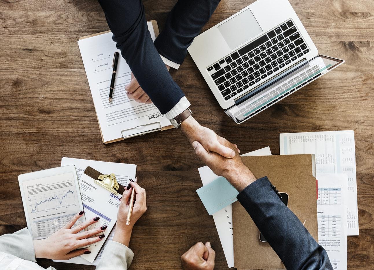 Ein Handschlag über einen Tisch mit Laptop und verschiedenen Papieren hinweg.