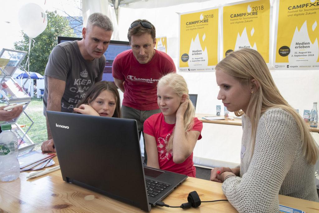 Eltern und ihre Kinder schauen auf einen Laptop.