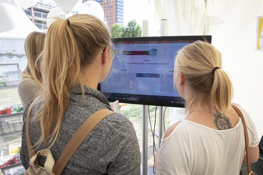 Zwei Teilnehmerinnen schauen auf einen Bildschirm.