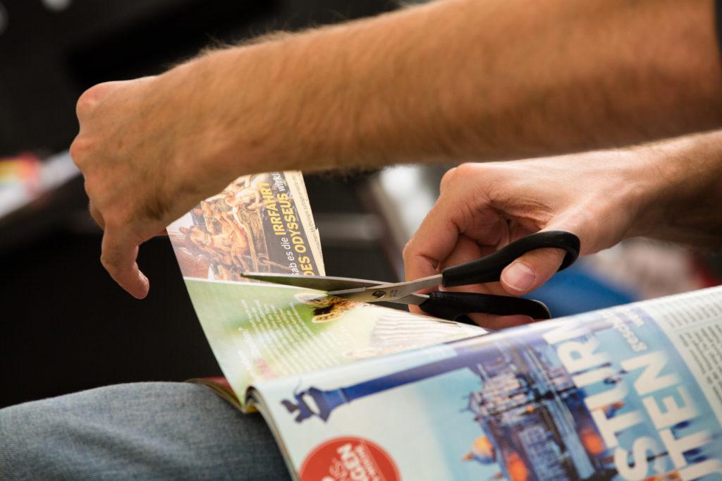 Hand schneidet Artikel aus Zeitung aus.