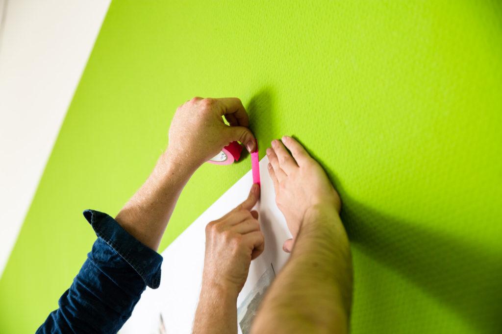 Hände kleben Zettel an die Wand.
