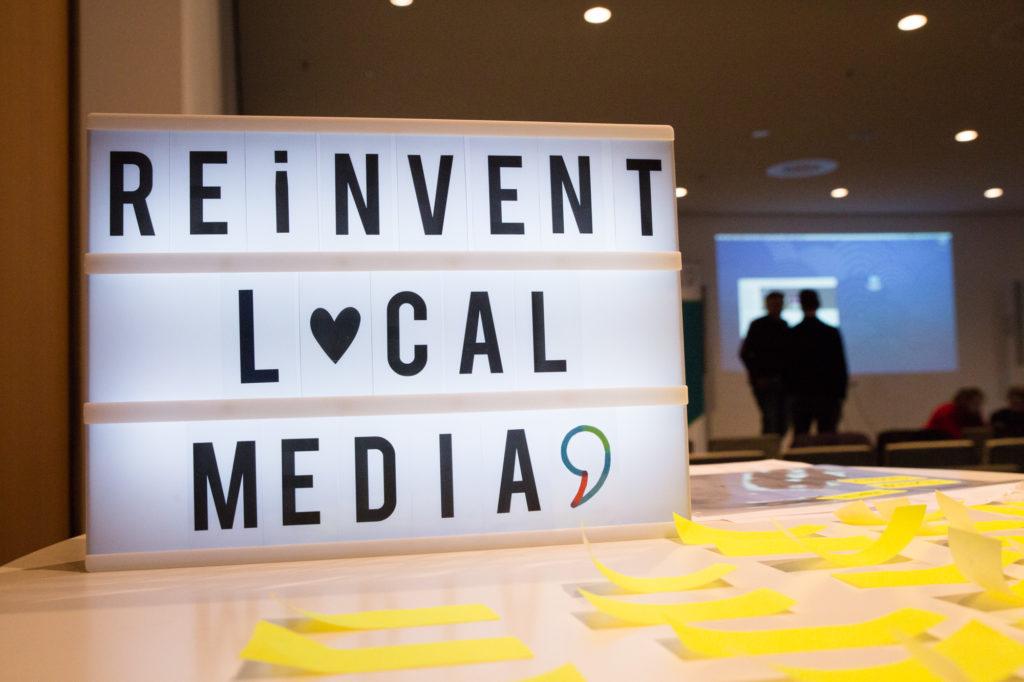 """Leuchtender Schriftzug """"Reinvent Local Media""""."""