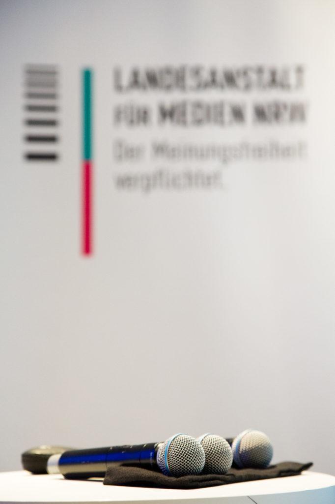Mikrofone vor Logo der Landesanstalt für Medien NRW.
