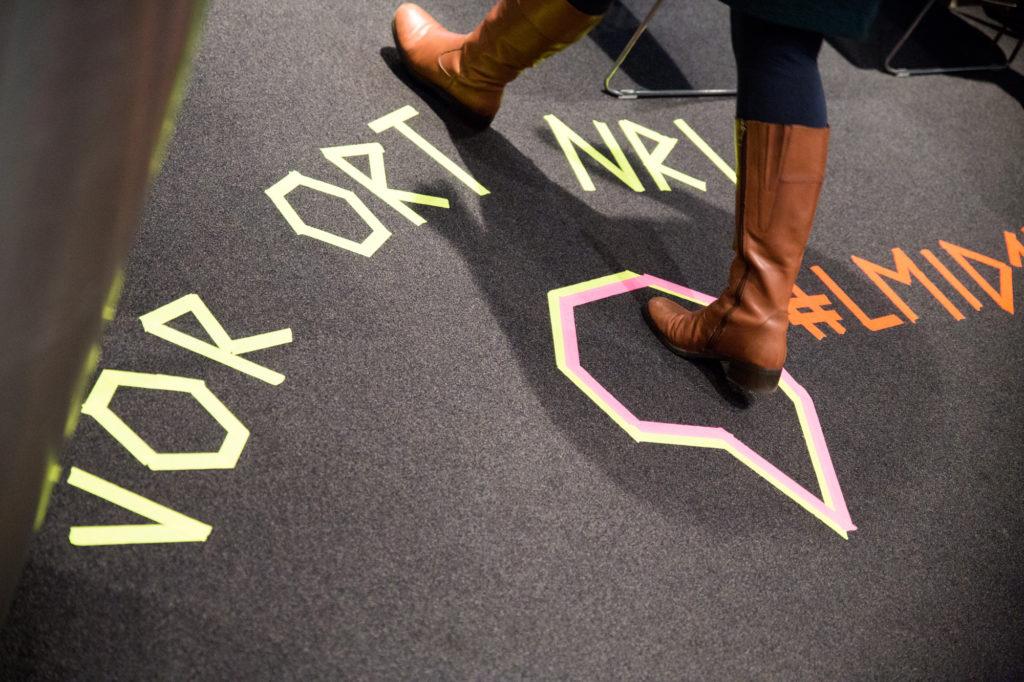 Teilnehmerin läuft über Teppich mit Grafik.