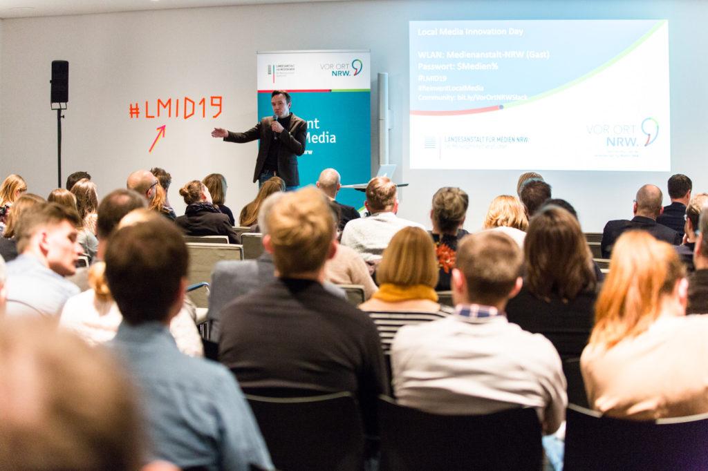 Publikum hört einer Präsentation zu.