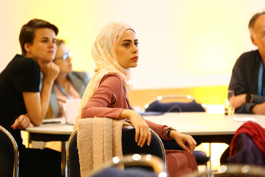Teilnehmerinnen und Teilnehmer hören gespannt zu.