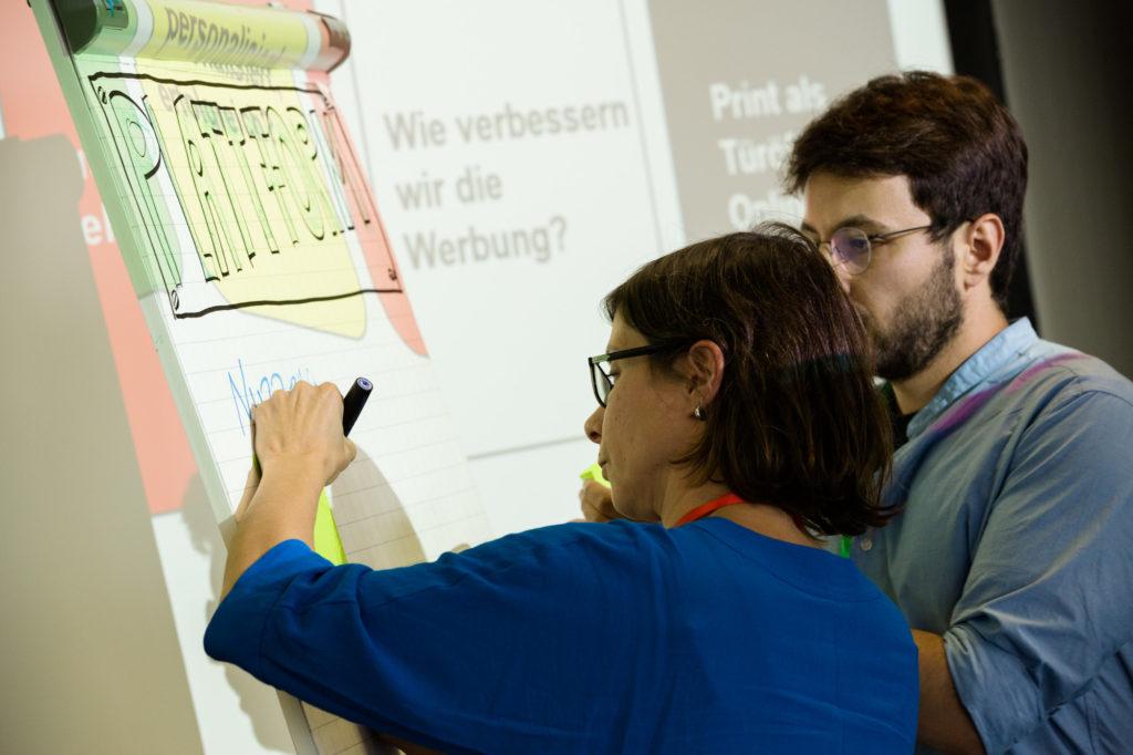 Die Teilnehmerinnen und Teilnehmer arbeiten mit Whiteboards.