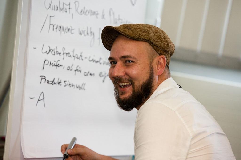 Ein Teilnehmer des Zahltags beschriftet ein Whiteboard.
