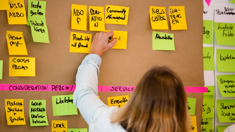 Eine Teilnehmerin schreibt etwas auf einen Notizzettel an einer Stellwand.