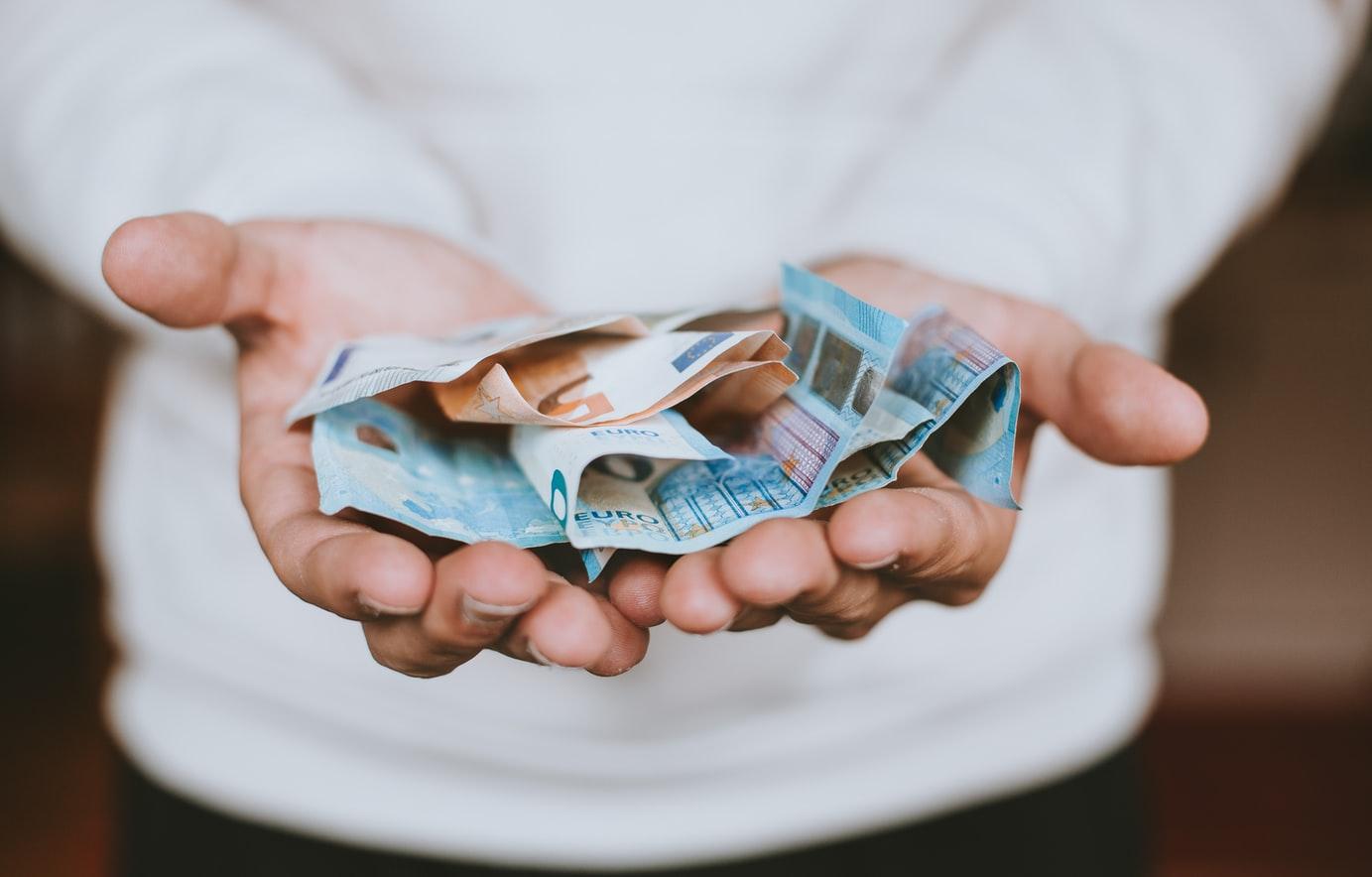 Hände mit Geldscheinen.