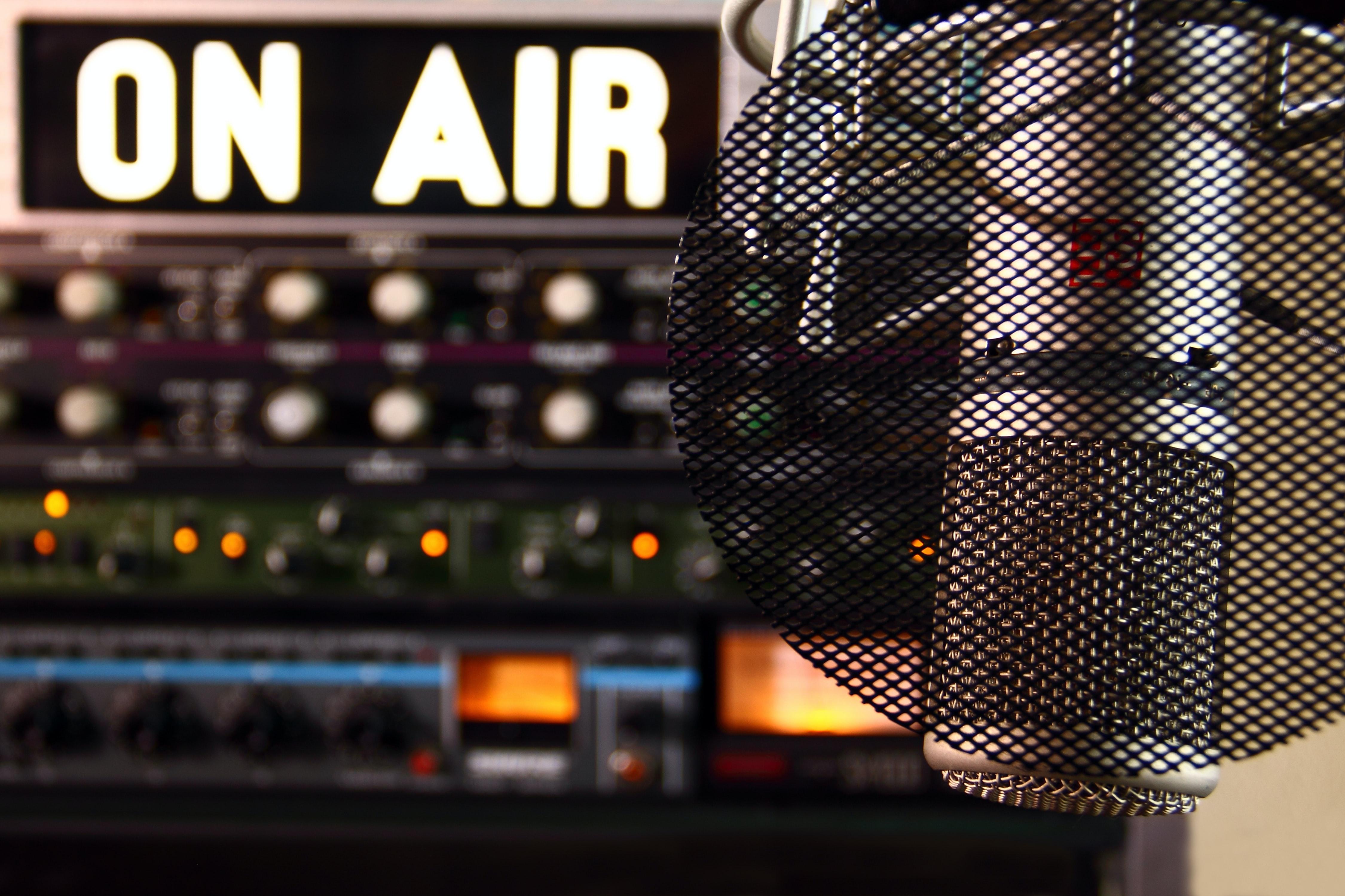 """Mikrofon vor Mischpult. Leuchtschrift """"on air"""""""