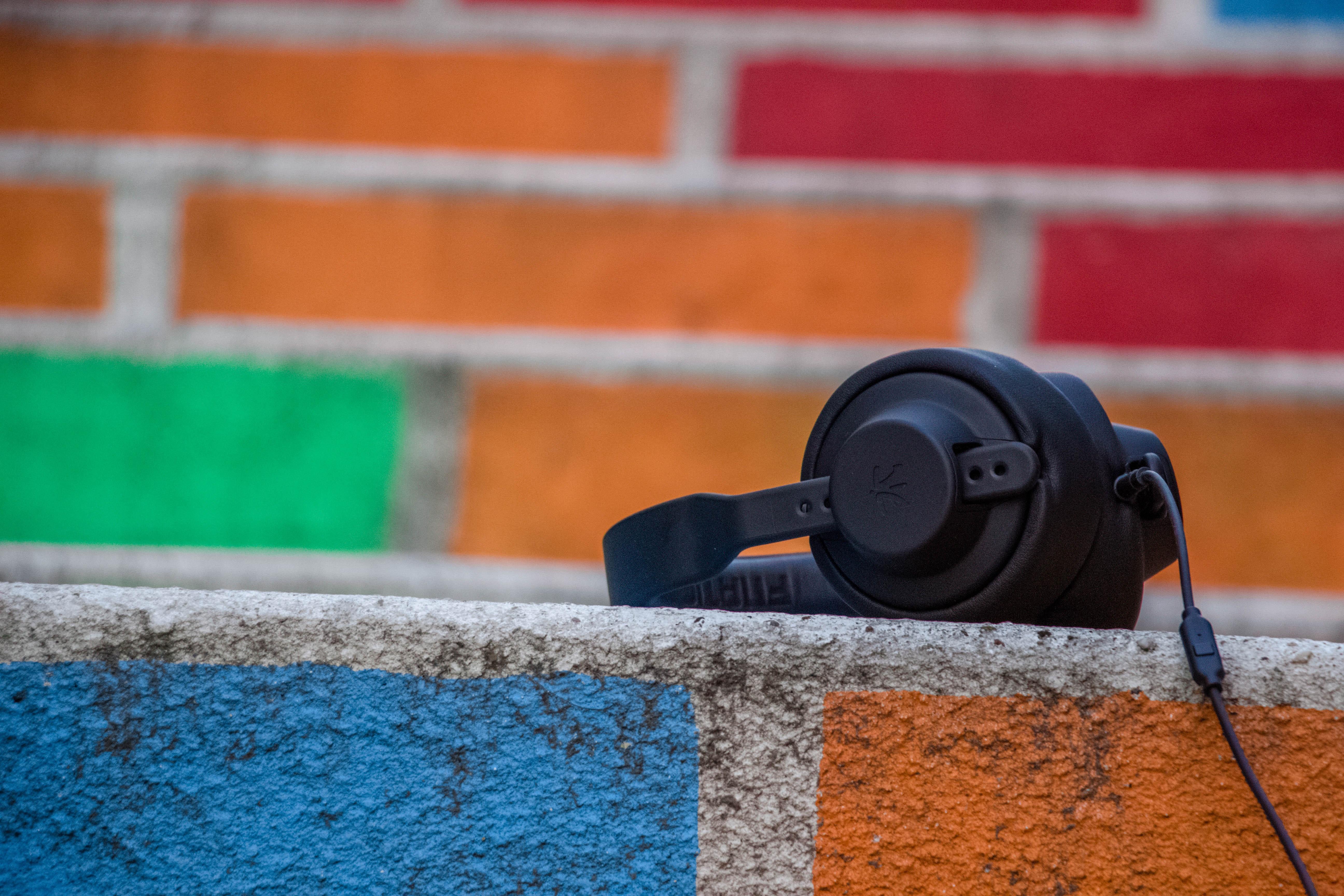 schwarzer Kopfhörer liegt auf Mauer aus bunten Backsteinen
