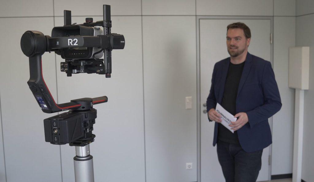 Moderator steht vor Kamera-Roboter