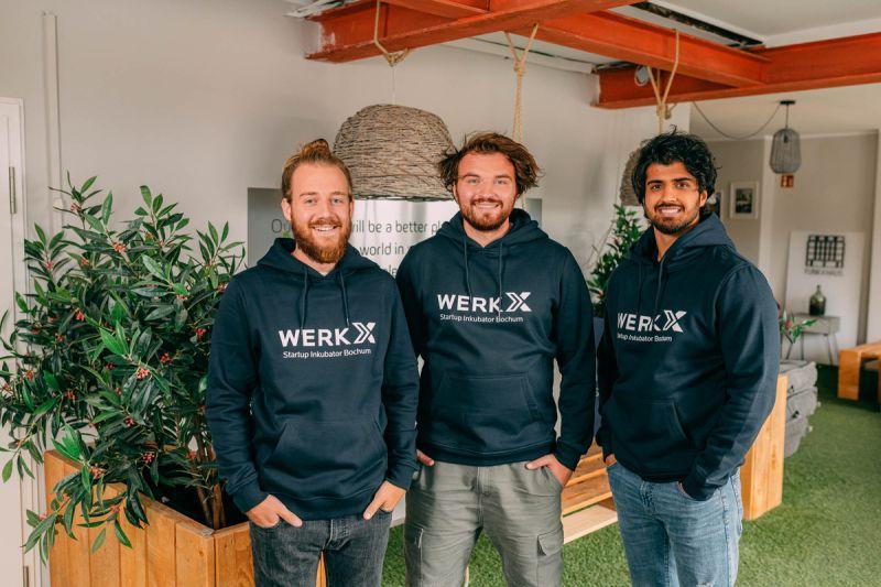 Die Drei Gründer von Novaheal stehen in schwarzen Pullis nebeneinander und lachen